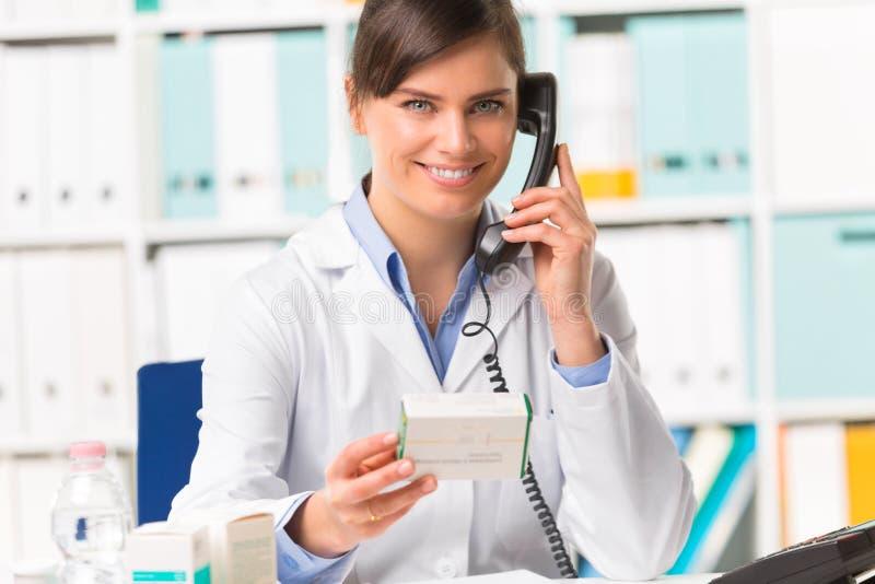 Farmacista femminile sorridente sulla medicina della tenuta del telefono immagine stock libera da diritti