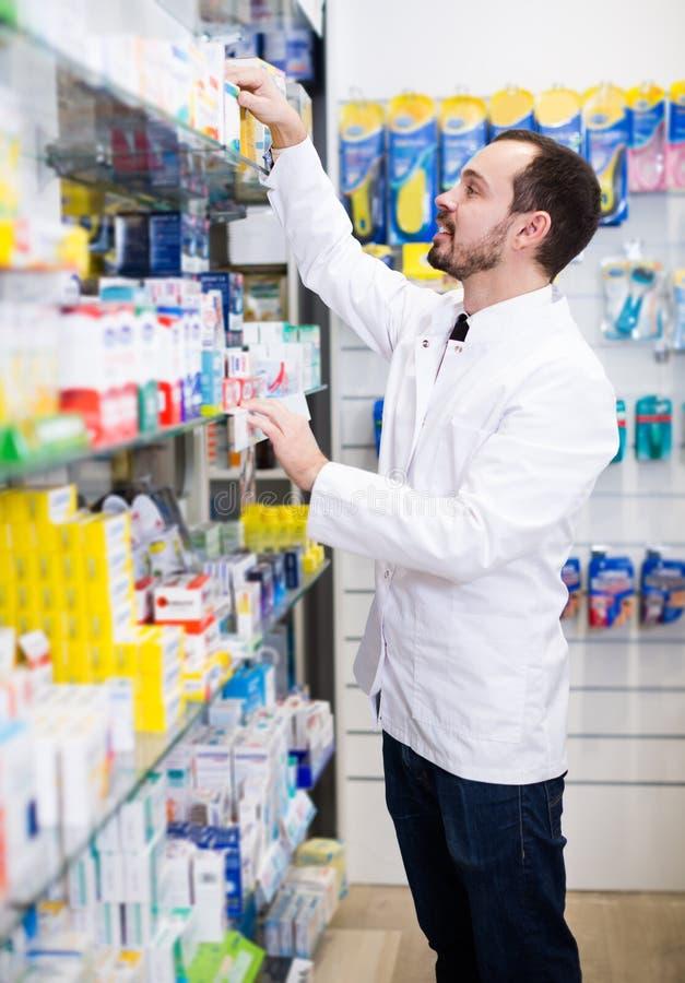 Farmacista maschio sorridente che cerca le file delle droghe fotografia stock