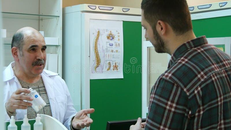 Farmacista senior che parla con cliente maschio mentre prendendo medicina dello scaffale immagini stock libere da diritti