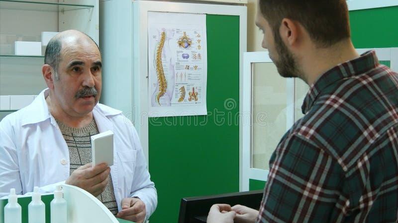 Farmacista senior e giovane cliente che discutono i farmaci fotografia stock libera da diritti