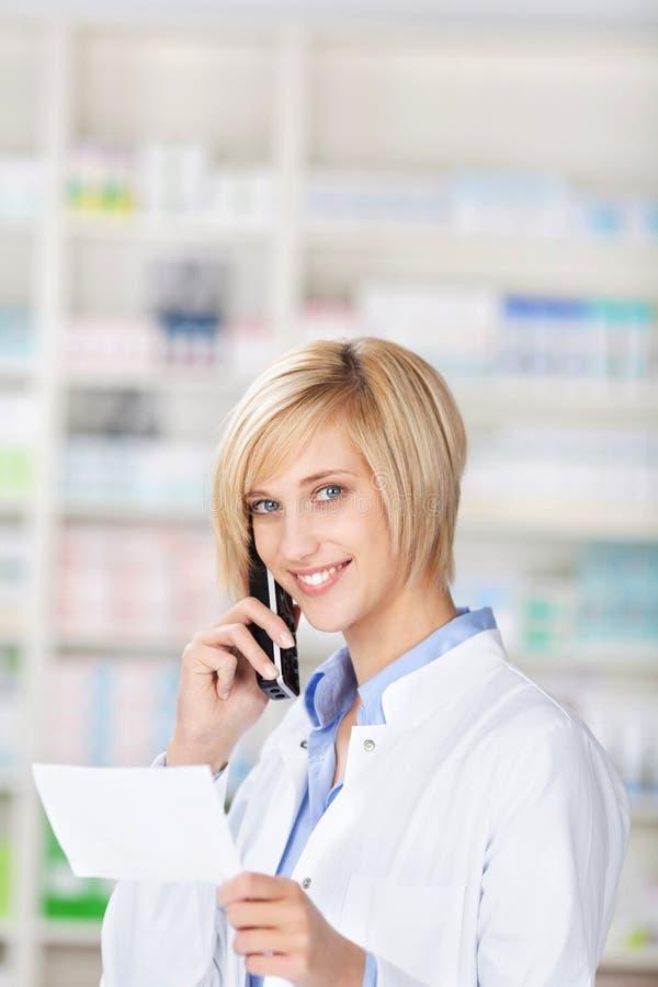 Farmacista sorridente che per mezzo del telefono fotografia stock libera da diritti