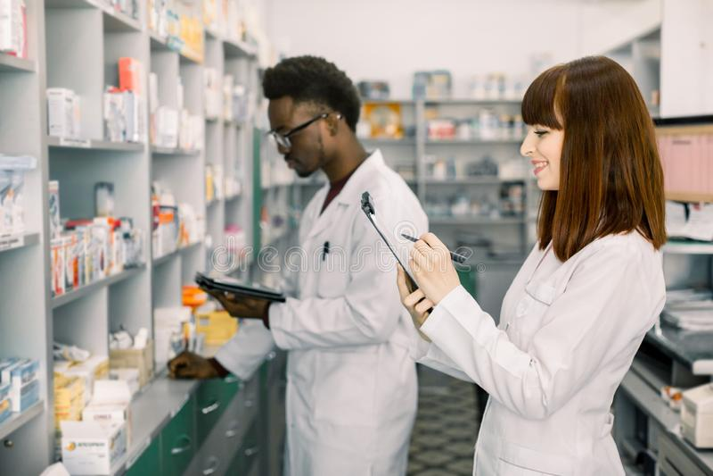 Farmacisti maschii e femminili sicuri in farmacia Farmacista maschio afroamericano che lavora alla compressa digitale e fotografia stock libera da diritti