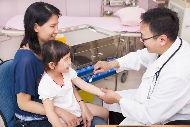 Farmaco dello sfregamento del pediatra sulla ferita del braccio della bambina fotografie stock libere da diritti