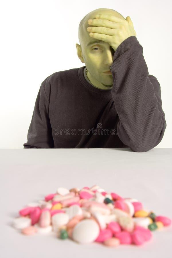 Farmaco Eyeing dell'uomo ammalato immagini stock libere da diritti