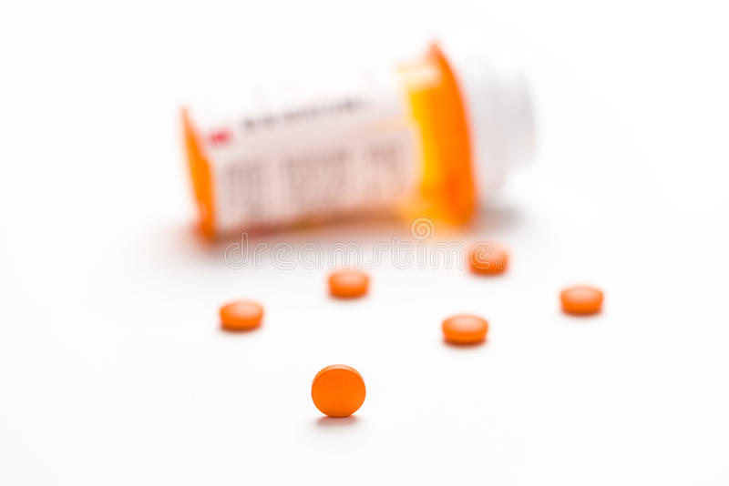 Farmaco, pillole che si rovesciano fuori su una superficie bianca fotografie stock