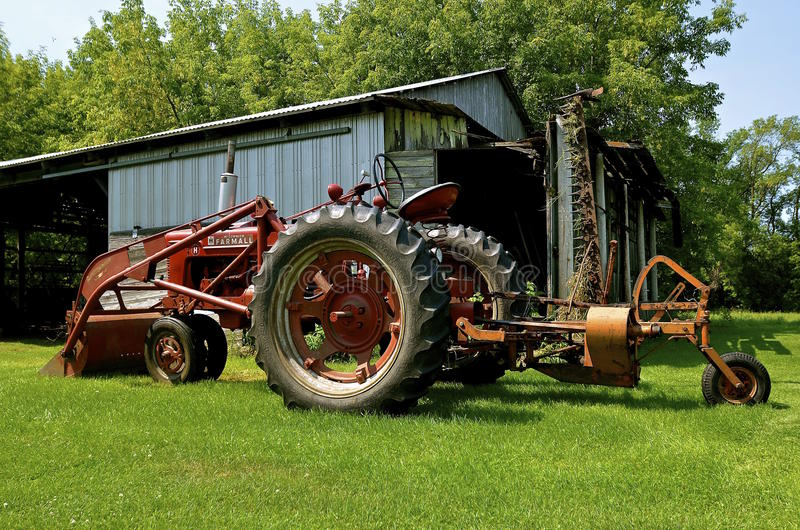 Farmall M tractor, front end loader, and lawn mower. RURAL MINNESOTA, Aug 23, 2015: The Farmall M and front end loader were model name and later a brand name for royalty free stock photography