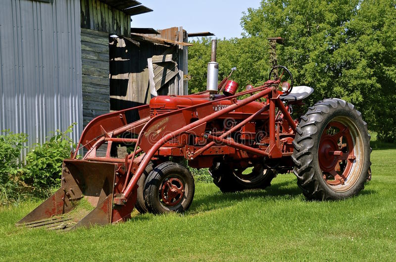 Farmall M tractor with front end loader. RURAL MINNESOTA, Aug 23, 2015: The Farmall M and front end loader were model name and later a brand name for tractors stock images