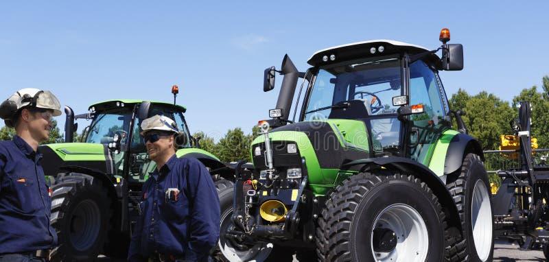 Farmer και μηχανικός με τα μεγάλα τρακτέρ στοκ εικόνα