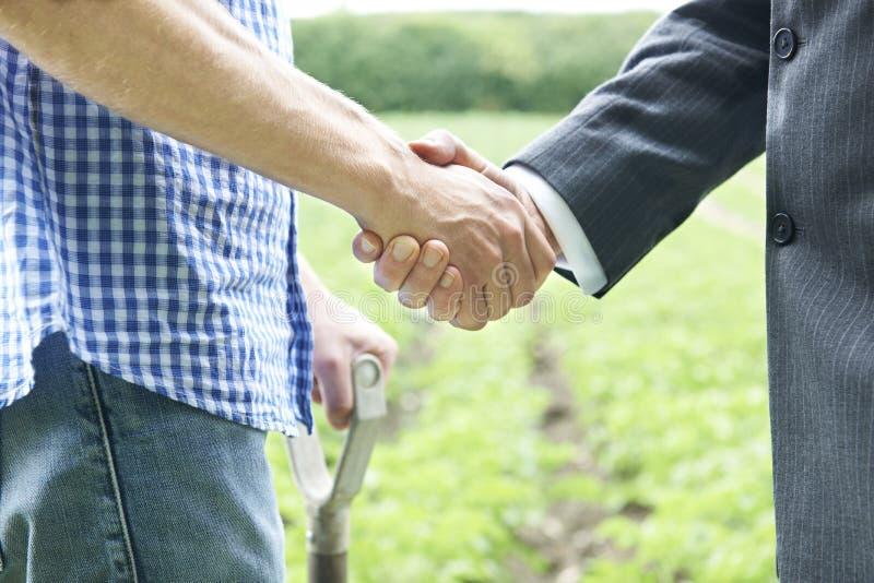 Farmer και χέρια τινάγματος επιχειρηματιών στοκ φωτογραφία με δικαίωμα ελεύθερης χρήσης