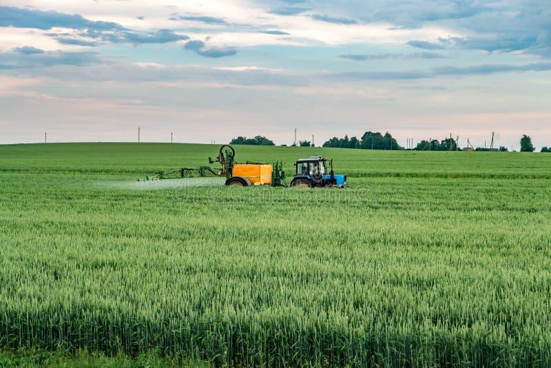 Farmer που ψεκάζει τον τομέα σίτου με τον ψεκαστήρα τρακτέρ στην εποχή άνοιξης στοκ εικόνα με δικαίωμα ελεύθερης χρήσης