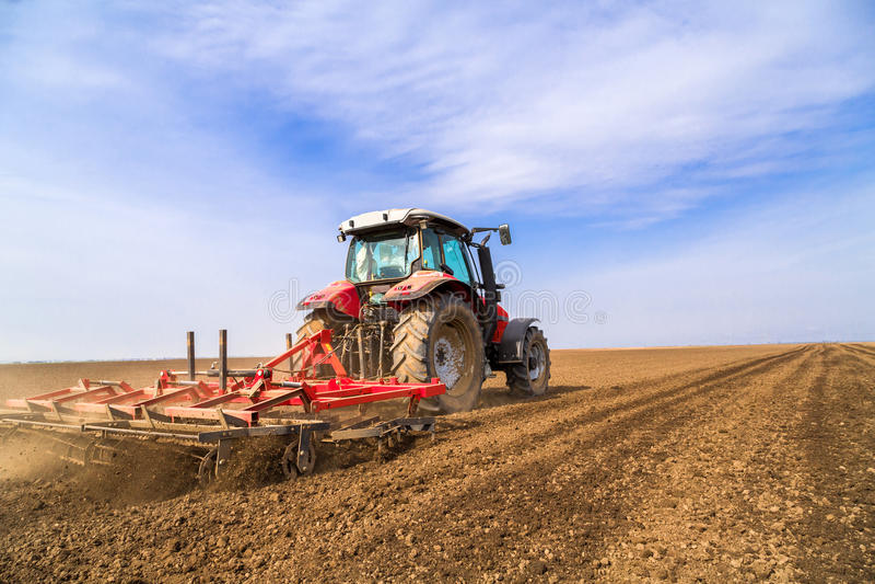 Farmer στο τρακτέρ που προετοιμάζει το έδαφος με τον καλλιεργητή φυτωρίων στοκ εικόνες