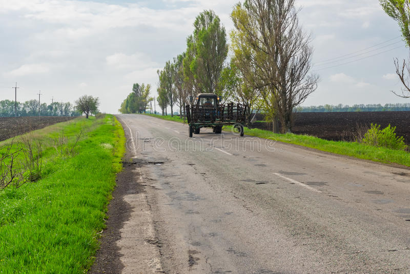 Farmer' 运输在最近的领域的s拖拉机耙在春季 免版税图库摄影