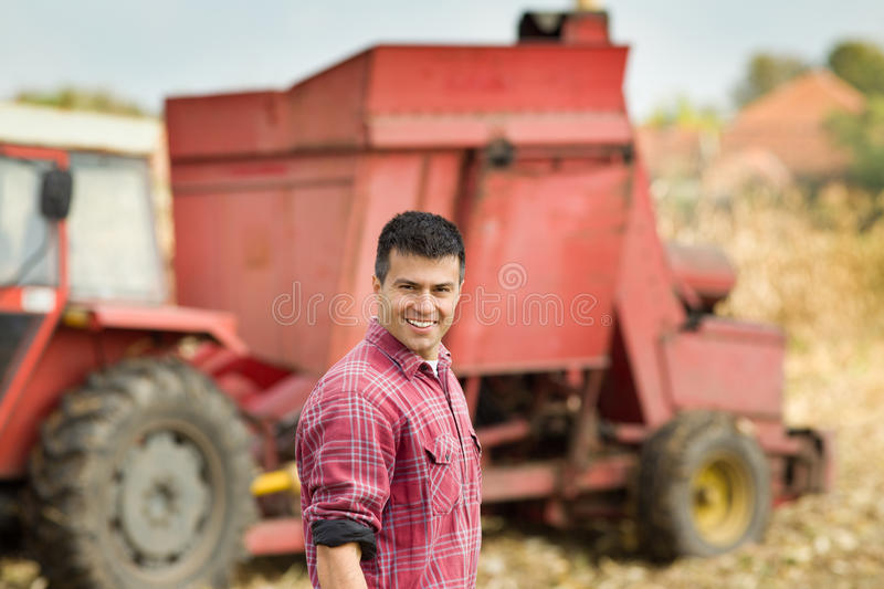 Farmer with agricultural machinery in field. Young satisfied farmer standing in front of agricultural machinery in corn field royalty free stock image