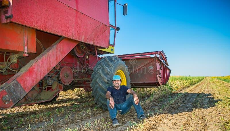 Farmer on a break. Sitting in a soybean field in shade near combine stock photography