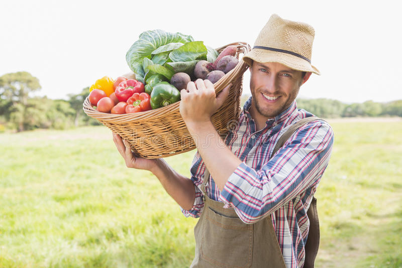 Farmer carrying basket of veg stock photos
