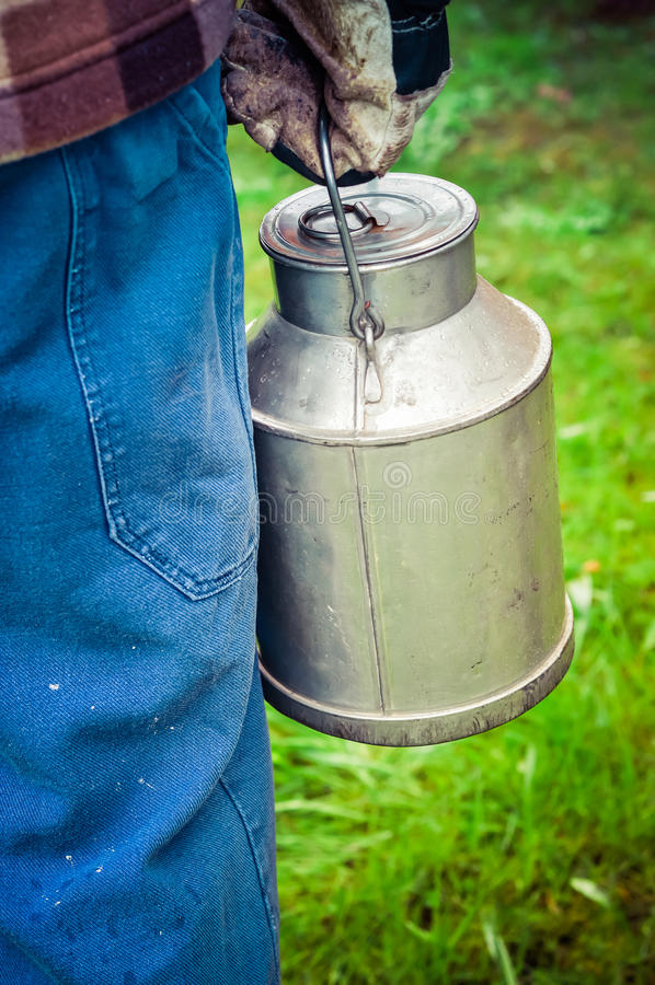 Farmer carrying a vintage dairy milk can. Farmer carrying a vintage dairy cream/ milk can. Farmer in dirty blue work trousers, plaid shirt and gloves goes royalty free stock images
