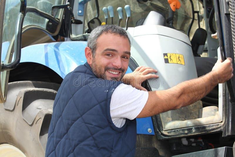 Farmer climbing into tractor royalty free stock image