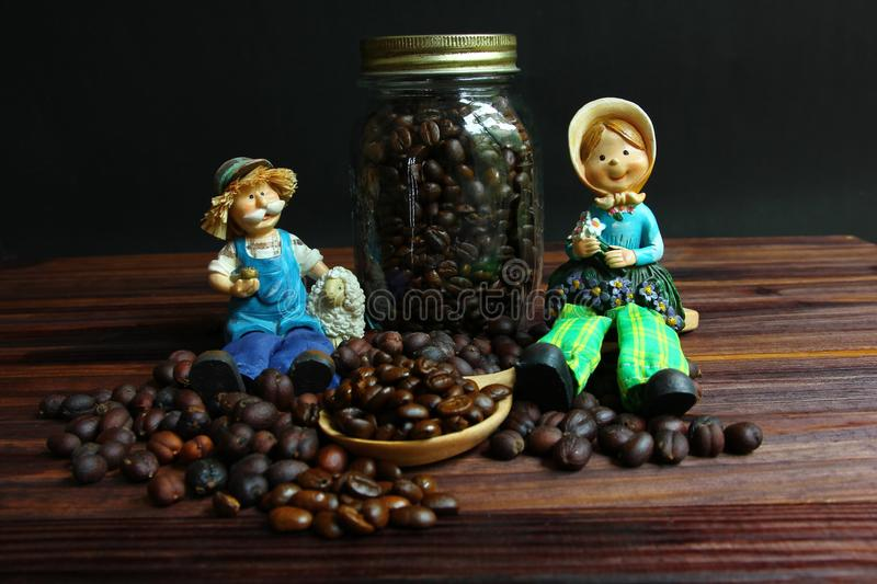 Farmer dolls sit on coffee beans.dried coffee beans with roasted coffee beans . stock images