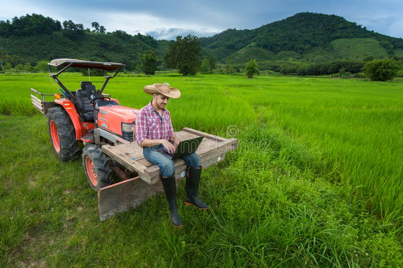 The farmer drinks water to relieve thirst on the tractor. On his stock photos