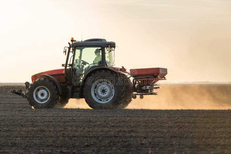 Farmer fertilizing arable land royalty free stock photography