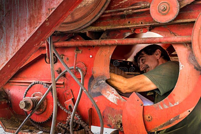 Farmer fixing combine stock photo