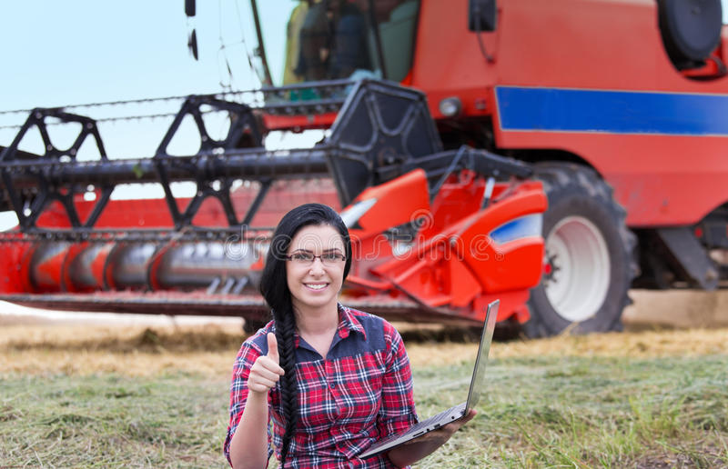 Farmer girl with laptop and combine harvester royalty free stock image