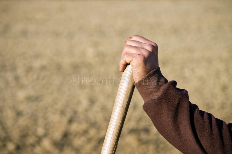 Farmer hand resting on wooden shovel or rake grip stock photos
