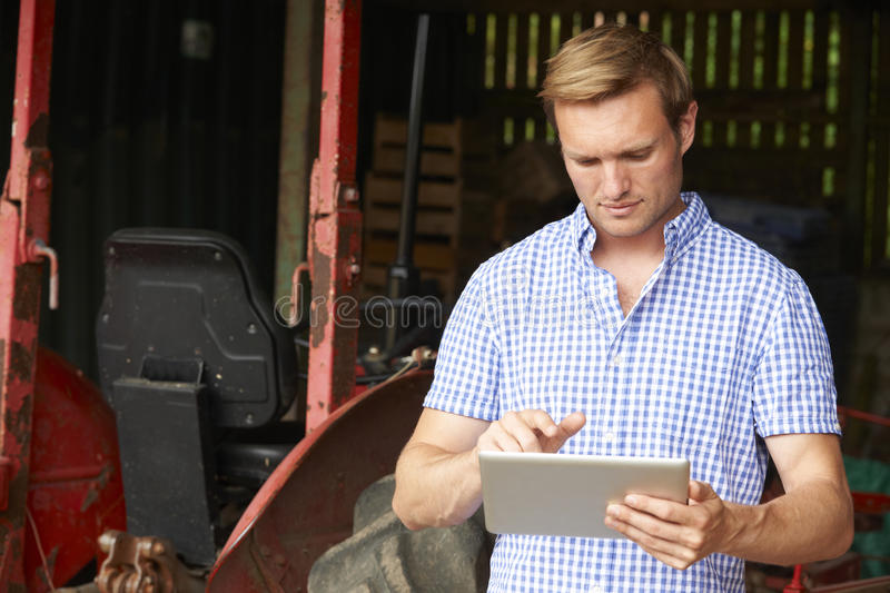 Farmer Holding Digital Tablet Standing In Barn With Old Fashioned Tractor royalty free stock image
