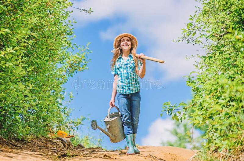 Farmer little girl. garden tools, shovel and watering can. kid worker sunny outdoor. family bonding. spring country side royalty free stock photo