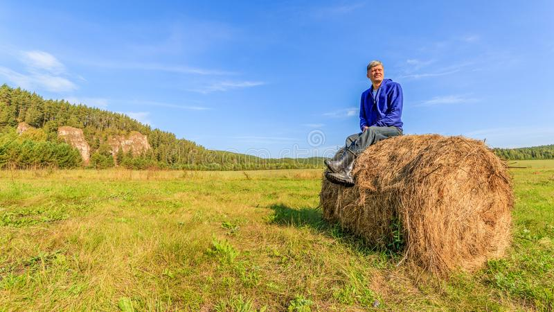 A farmer sits on straw bales on the field. royalty free stock photos