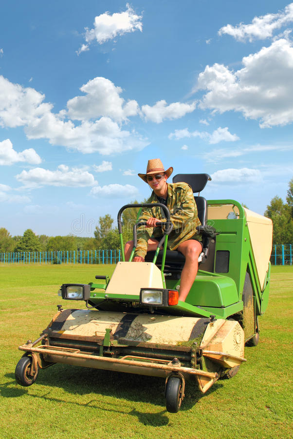 Farmer Mowing the Lawn. A young smiling farmer mowing the lawn on a tractor stock image