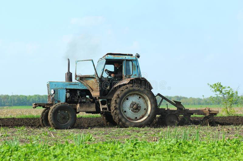 Farmer plowing and cultivating field on tractor. stock photo