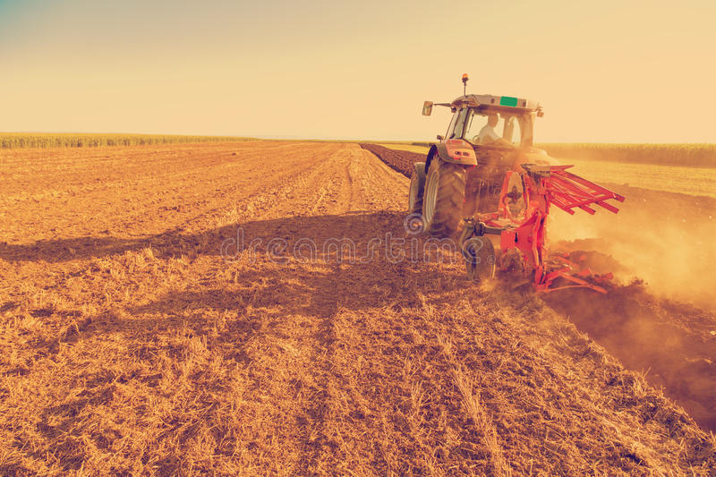 Farmer plowing stubble field with red tractor stock images