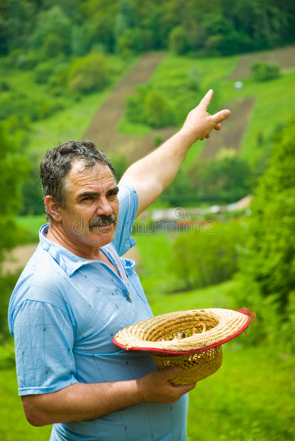 Farmer pointing to his plowing land on hill stock images