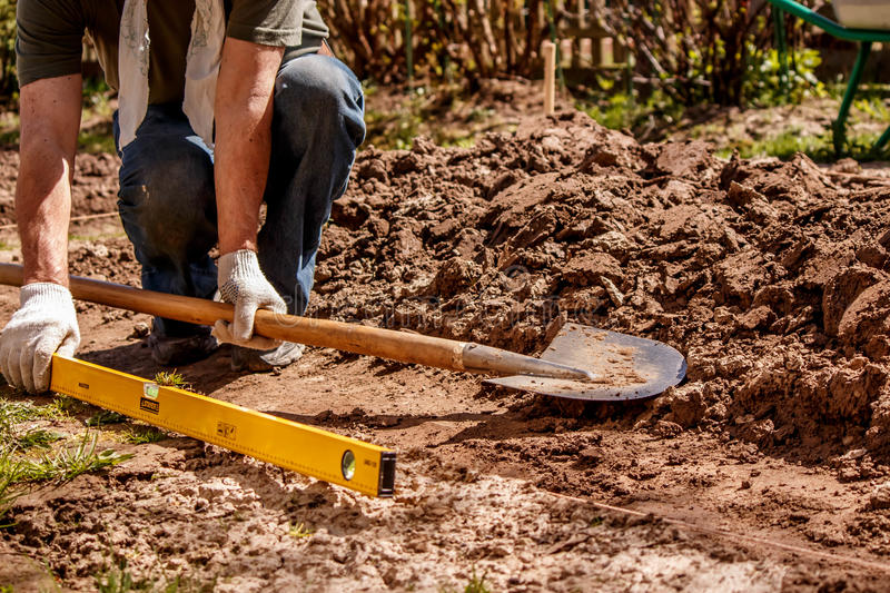 The farmer prepares the place for the greenhouse using a level and a shovel stock photography