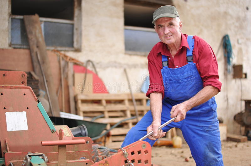 Farmer Repairing His Red Tractor Royalty Free Stock Photography