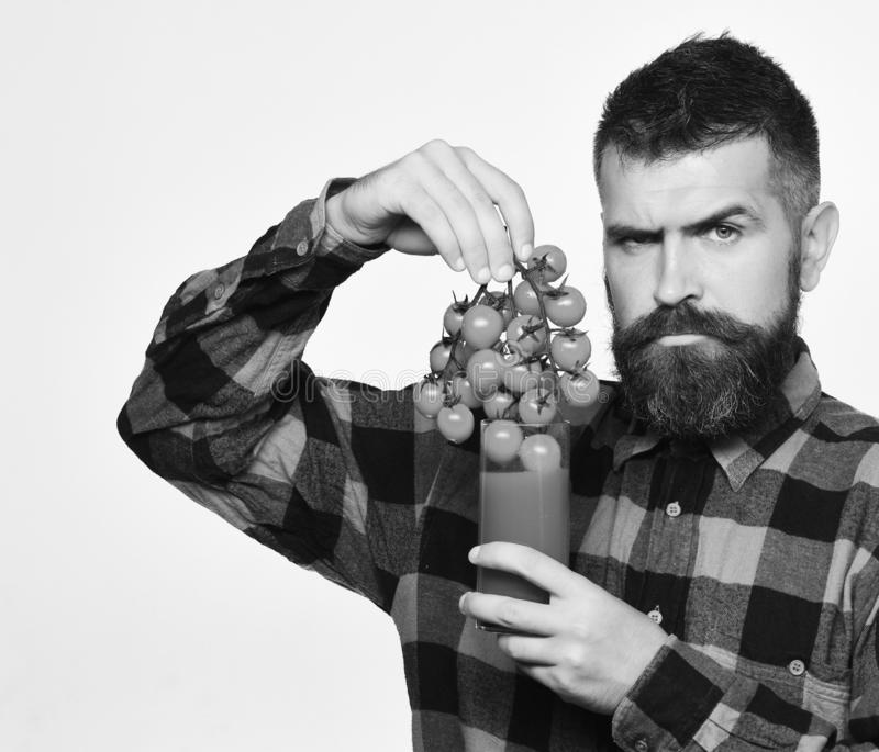 Farmer with serious face shows bunch of red cherry tomatoes. Man with beard holds glass of juice and vegetables on white background. Guy holds homegrown stock photos