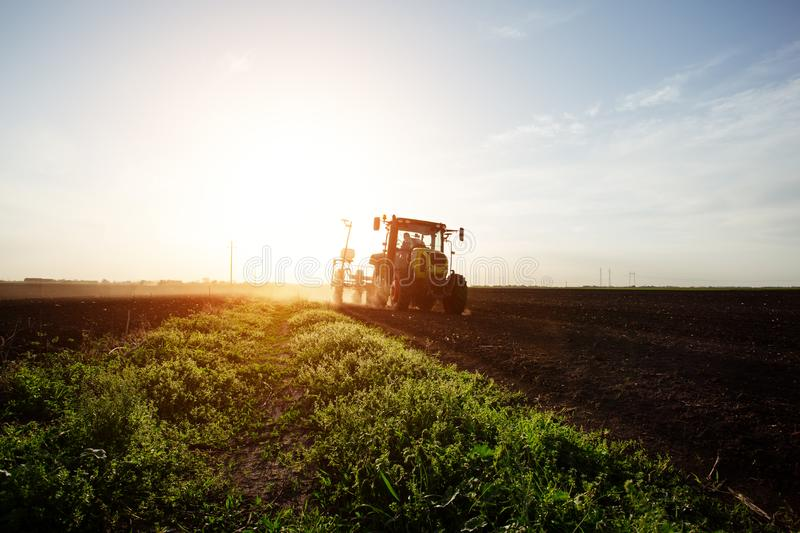 Farmer sowing crops at field with tractor. - Image stock images
