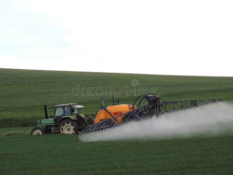 Farmer spraying chemicals in the fields. Near a wood in France stock photos