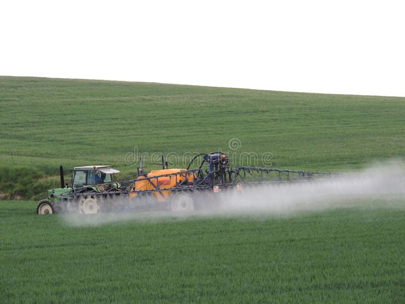 Farmer spraying chemicals in the fields. Near a wood in France stock photography