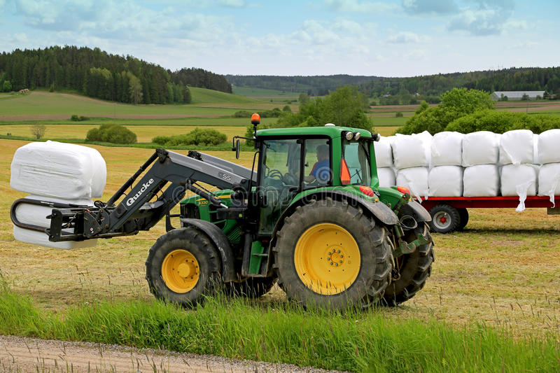 Farmer Stacks up Silage with Front Loader John Deere 6330 Tractor stock photo