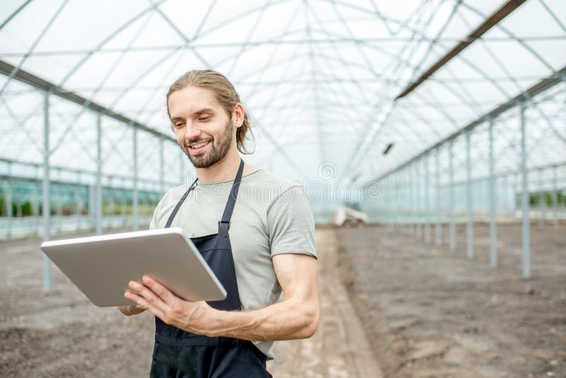 Farmer with tablet in the glasshouse. Handsome farmer working with digital tablet standing in the glasshouse with cultivated soil royalty free stock image