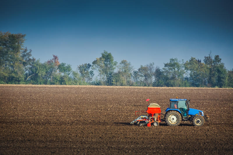 Farmer with tractor seeding crops in the field royalty free stock photo