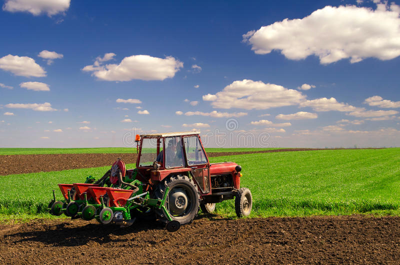 Farmer with tractor sowing on agricultural fields in spring. Farmer with tractor sowing on agricultural fields on sunny spring day stock photography