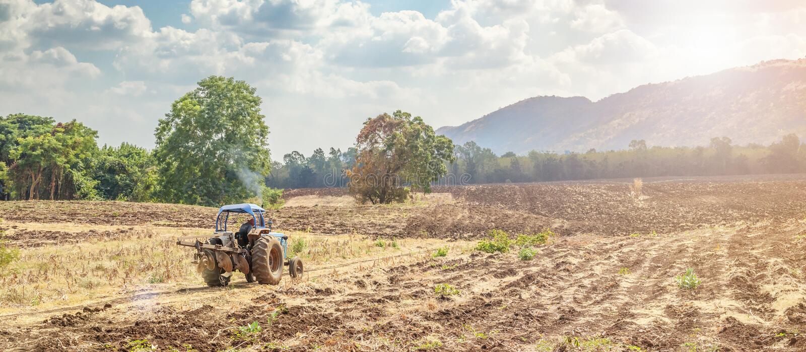 Farmer in tractor working and preparing land in agriculture field with mountain stock photos