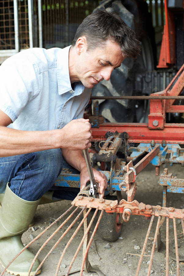 Farmer Working On Agricultural Equipment In Barn. Farmer Works On Agricultural Equipment In Barn royalty free stock image