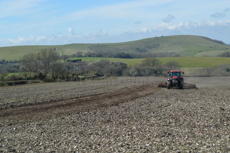 Farmer working his crop field in Sussex. stock photography