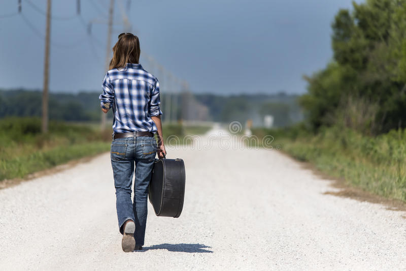 Farmers Daughter. Female walking down a dirt road hitchhiking with a guitar case royalty free stock images