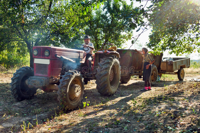 Farmers family with tractor. Family of senior farmers with an old tractor with trailers in an orchard of plum trees royalty free stock image