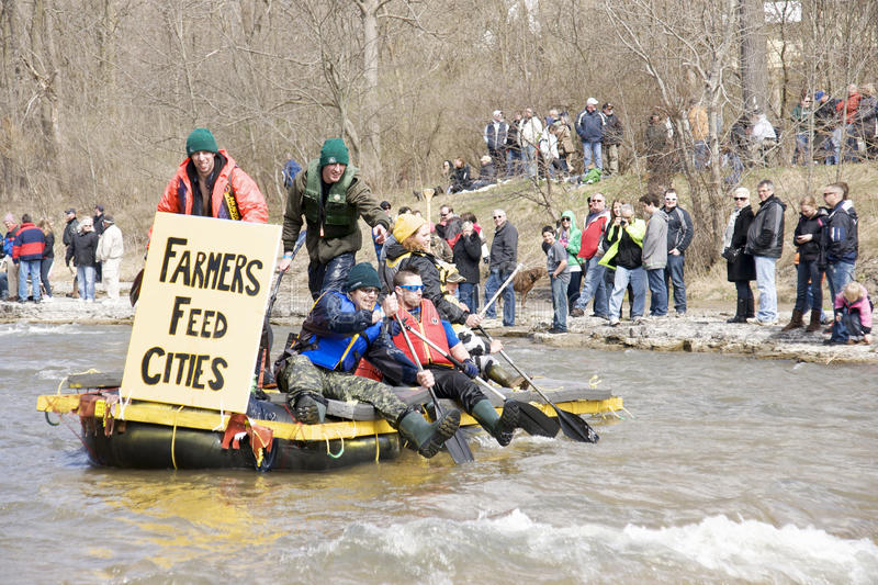 Farmers Feed Cities Raft- Port Hope, March 31/2012. Participants paddle a home made raft through the Ganaraska River rapids on March 31, 2012 in Port Hope stock images